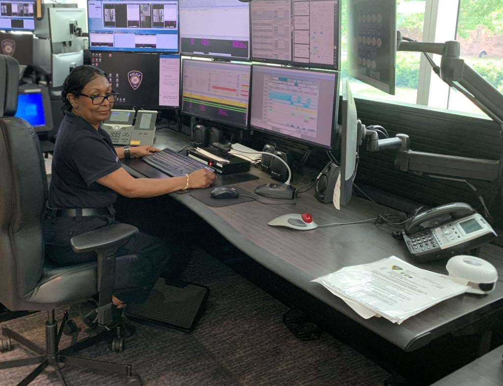 Dispatcher sits at Russ Bassett console in Yale University's Public Safety center